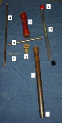 Equipamentos para obtenção de amostras de solo: a) haste para martelo deslizante (parafuse a haste na cabeça guia), b) martelo deslizante, c) tampa para reter o solo no tubo de plástico, d) tubo de plástico - interno, e) haste para remover amostra (deslizar ao longo do furo na cabeça guia), f) pino para anexar (d)